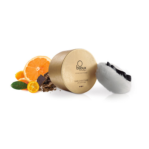 An image of the bijoux kissable body powder round gold container with application puff. Next to it are oranges and chocolate, to indicate the dark chocolate and citrus flavor.