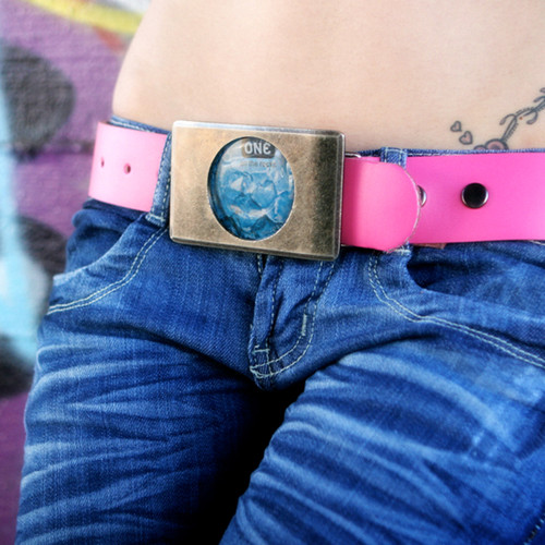 An image of a woman's hips wearing blue jeans held up by the stylish pink lovebuckle belt.