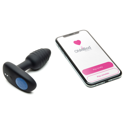 An image of the Lumen Bluetooth enabled plug lying on a white surface with a smartphone displaying the OhMiBod Remote App