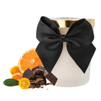 An image of the bijoux Melt By Heart dark chocolate scented massage candle. It is in a jar with a black ribbon. Next to it are oranges and chocolate, to indicate the dark chocolate and citrus flavor.