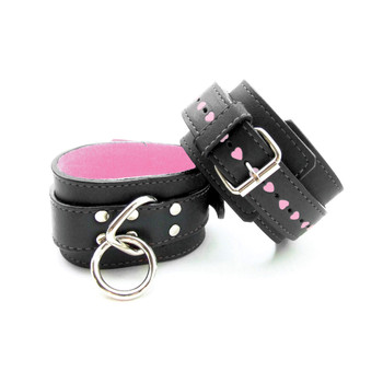 An image of black leather buckled wrist cuffs with soft pink interior and rows of little pink hearts along the straps.