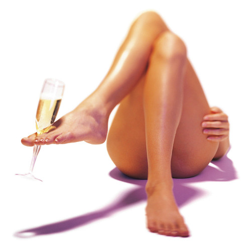 Erotic photography from The New Intercourses. A naked woman lies on her back, her legs visible to the viewer, as she holds a flute of champagne with her foot.