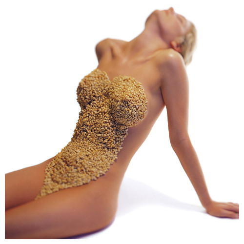 Erotic photography from The New Intercourses. A naked woman sits with her back arched, her front covered in nuts and seeds.