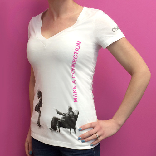 An image of the torso of a woman wearing the white V-neck Make a Connection OhMiBod t-shirt standing against a pink background.
