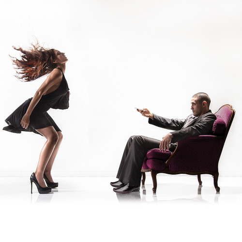 An image of a man and a woman, the woman dancing and the man holding his phone as he sits in front of her, controlling her wearable vibe.